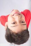 Kleiner Junge, der oben mit dem Lächeln auf weißem Hintergrund schaut Lizenzfreie Stockfotos