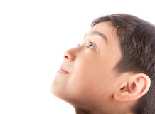 Kleiner Junge, der oben mit dem Lächeln auf weißem Hintergrund schaut Stockbild