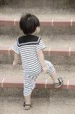 Kleiner Junge, der oben Treppe geht Stockfoto
