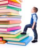 Kleiner Junge, der oben zu großen Staplungsbüchern schaut Stockfotos