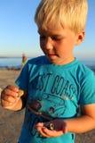 Kleiner Junge, der Oberteile auf dem Strand sammelt Stockfoto