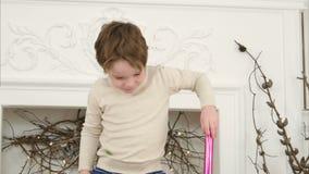 Kleiner Junge, der Papierrolle als Spionsglas verwendet und Packpapierklingenkampf mit seiner Mutter hat stock video