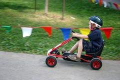 Kleiner Junge, der Pedal Kart läuft Stockfoto