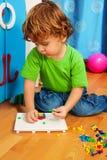 Kleiner Junge, der Puzzlespiel löst Stockfotos