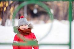 Kleiner Junge in der roten Winterkleidung, die Spaß auf Spielplatz im Freien hat Lizenzfreies Stockbild