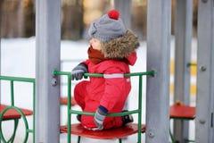 Kleiner Junge in der roten Winterkleidung, die Spaß auf Spielplatz im Freien hat Stockbilder
