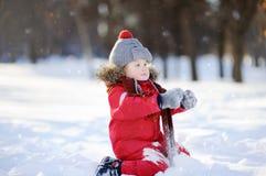Kleiner Junge in der roten Winterkleidung, die Spaß mit Schnee hat Stockbilder