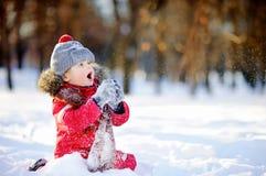 Kleiner Junge in der roten Winterkleidung, die Spaß mit Schnee hat Stockfotografie