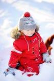 Kleiner Junge in der roten Winterkleidung, die Spaß mit Schnee hat Lizenzfreies Stockfoto