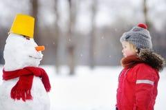 Kleiner Junge in der roten Winterkleidung, die Spaß mit Schneemann hat Stockbilder