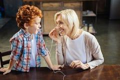 Kleiner Junge der Rothaarigen, der Kopfhörer mit Oma teilt lizenzfreie stockfotografie