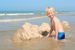 Kleiner Junge, der sandigen Strand genießt Lizenzfreie Stockfotografie