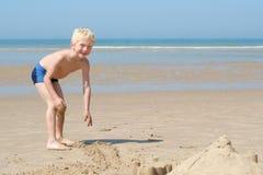Kleiner Junge, der sandigen Strand genießt Stockbild
