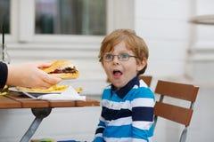 Kleiner Junge, der Schnellimbiß isst: Pommes-Frites und Hamburger stockfotos