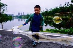 Kleiner Junge, der Seifenblasen macht Lizenzfreie Stockfotos