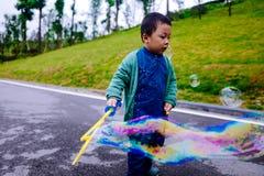 Kleiner Junge, der Seifenblasen macht Stockbild