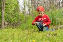 Kleiner Junge, der sein eigenes Lagerfeuer beleuchtet Lizenzfreie Stockfotografie