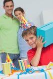 Kleiner Junge, der sein Geburtstagsgeschenk rüttelt Lizenzfreie Stockbilder