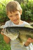 Kleiner Junge, der sein neues Fang upclose vorführt Stockbilder