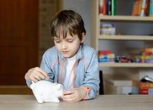 Kleiner Junge, der seine Einsparung zu seinem Sparschwein setzt Lizenzfreies Stockbild