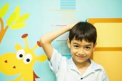 Kleiner Junge, der seine Höhe am Krankenhausheranwachsen überprüft Lizenzfreies Stockfoto
