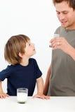 Kleiner Junge, der seine Trinkmilch des Vaters überwacht stockfoto