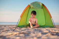Kleiner Junge, der in seinem Zelt auf dem Strand spielt Stockfotos