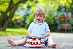 Kleiner Junge, der seinen Geburtstag im Garten des Ausgangs mit großem Ca feiert Stockbild