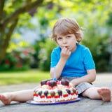 Kleiner Junge, der seinen Geburtstag im Garten des Ausgangs mit großem Ca feiert Stockfoto