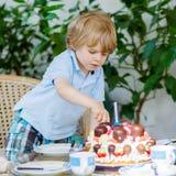 Kleiner Junge, der seinen Geburtstag im Garten des Ausgangs mit großem Ca feiert Lizenzfreie Stockfotografie