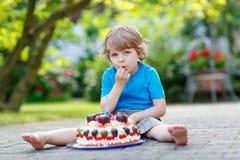 Kleiner Junge, der seinen Geburtstag im Garten des Ausgangs mit großem Ca feiert Lizenzfreies Stockfoto