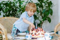 Kleiner Junge, der seinen Geburtstag im Garten des Ausgangs mit großem Ca feiert Stockbilder