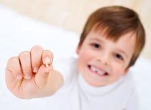 Kleiner Junge, der seinen Milchzahn in seiner Hand zeigt Lizenzfreies Stockfoto