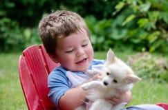Kleiner Junge, der seinen Welpen betrachtet Lizenzfreies Stockfoto