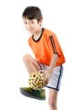Kleiner Junge, der sepak takraw auf weißem Hintergrund nimmt Lizenzfreies Stockfoto