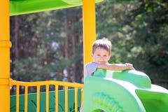 Kleiner Junge, der Spaß auf einem Spielplatz draußen im Sommer hat Lizenzfreie Stockfotos