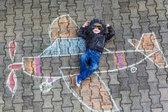 Kleiner Junge, der Spaß mit Flugzeugbildzeichnung mit Kreide hat Stockbilder