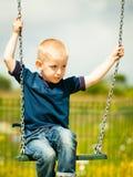 Kleiner Junge, der Spaß am Spielplatz hat Kinderkind, das auf einem Schwingen im Freien spielt Glückliche aktive Kindheit Lizenzfreie Stockfotografie
