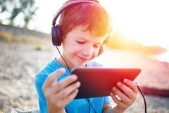 Kleiner Junge, der Spiel auf Tablette im Sonnenuntergang spielt lizenzfreie stockfotos
