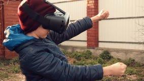 Kleiner Junge, der Spiel unter Verwendung des Kopfhörers der virtuellen Realität im Hinterhof laufend spielt stock video footage