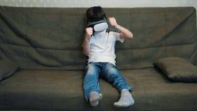 Kleiner Junge, der Spiel unter Verwendung des Kopfhörers der virtuellen Realität laufend sitzt auf dem Sofa palting ist stock video