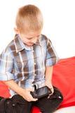Kleiner Junge, der Spiele auf Smartphone spielt Stockfotografie