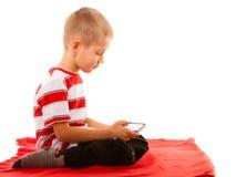 Kleiner Junge, der Spiele auf Smartphone spielt Stockfoto
