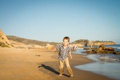 Kleiner Junge, der am Strand läuft Stockbild