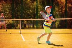 Kleiner Junge, der Tennis spielt Stockfotografie