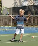 Kleiner Junge, der Tennis spielt Lizenzfreie Stockfotos