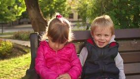Kleiner Junge, der trauriges kleines Mädchen auf einer Parkbank küsst stock footage