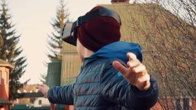 Kleiner Junge, der um tragenden Kopfhörer der virtuellen Realität im Hinterhof schaut stock video