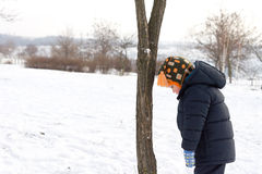 Kleiner Junge, der unten dem Winterschnee betrachtet Lizenzfreie Stockbilder