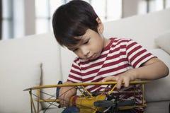 Kleiner Junge, der unten schaut und ein Flugzeugmodell, auf der Couch im Wohnzimmer hält Lizenzfreies Stockfoto